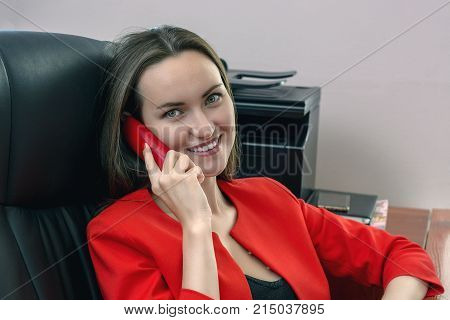 Smiling Woman In A Red Business Suit Sits In A Leather Chair And Talking On The Phone.