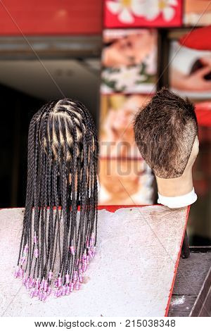 The hair on the mannequin. Examples of hairstyles for female and male mannequin head. Barber on the street of a tropical country. Many small braids. Sloppy short hair.