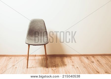 Chair stands near the wall in the empty room