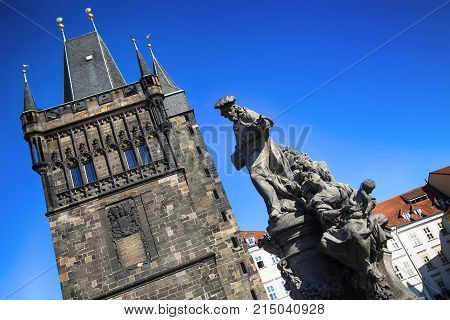 View of the Old Town Bridge Tower (Stare Mesto Tower) with statue on the Charles Bridge (Karluv Most) in Prague Czech Republic