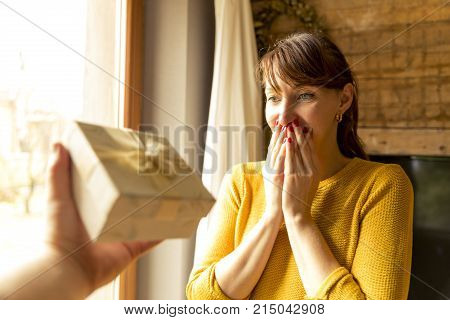 happy woman receiving a gift from husband by a window