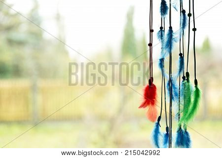 Beautiful dream catcher by a window with blue green and red feathers