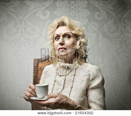 Senior rich woman having a cup of tea