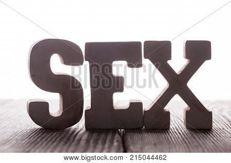The word sex from wooden letters stand on the table