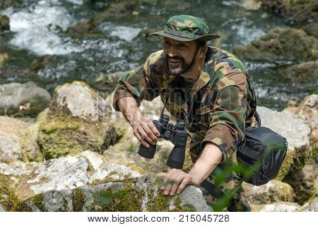 The smiling man in military uniform with binoculars is on adventure or expedition in nature.