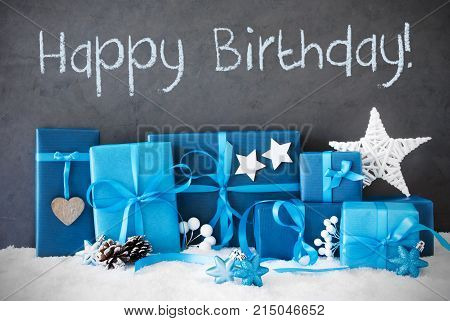 Concrete Wall With English Text Happy Birthday. Blue Christmas Gifts With Decoration Like Stars And Fir Cone On Snow.