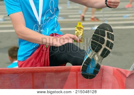 An athlete warms up his feet.She's resting after the marathon.