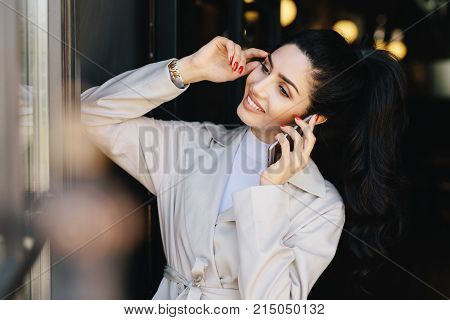 Elegant brunette slim woman with pony tail dressed in white coat having dark eyebrows, eyes, pure skin, nice manicure chatting over mobile phone touching her head with hand looking smiling aside