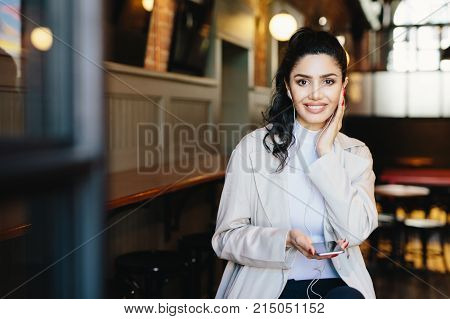 Happy brunette woman with make-up and manicure wearing white jacket holding smartphone and having earphones in ears listening to music or audiobook on earphones. Dreaming female in cafe using mobile