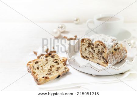 criststollen typical german christmas cake with raisins and fruits next to a cup of coffee cinnamon stars and baubles on a white wooden background with copy space selected focus narrow depth of field
