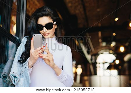 Elegant brunette woman with pure skin, wearing sunglasses, having red perfect manicure wearing white formal clothes holding cell phone using free Internet, checking her e-mails. People, communication