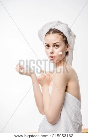 young surprised girl in white towel on head applying cleansing foam on face