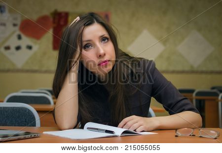 Tired and bored wistful student girl sits at the school desk and holds her head with her hand. Education concept. Fail exam concept.