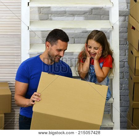 Father And Child With Excited Faces Look Into Box.