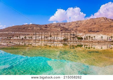 The concept of medical and ecological tourism. Therapeutic Dead Sea, Israel. Between the sea and dry mountains of red sandstone highway passes