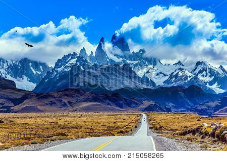 Summer day in Patagonia. Fine highway to the grandiose Mount Fitz Roy. The concept of active and extreme tourism. The Andean condors hover over the prairie