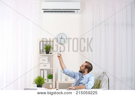 Young man with turning on air conditioner at table in office