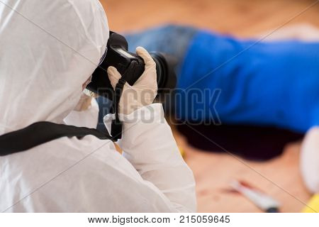 murder, investigation, forensic examination and people concept - criminalist with camera photographing dead male victim body at crime scene