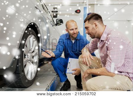 auto service, repair, maintenance and people concept - mechanic with clipboard showing tire to man or owner at car shop over snow