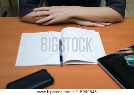 Female student sits in the class room holds her hands on a desk reads and prepares to pass exam. Education concept.