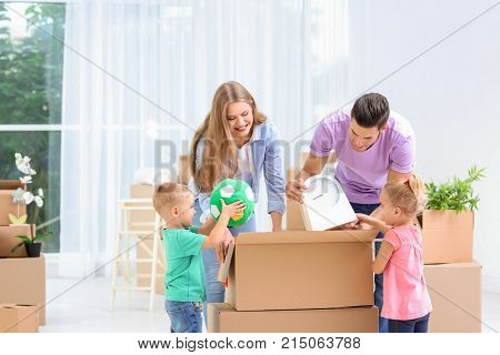 Happy family unpacking moving boxes in their new house