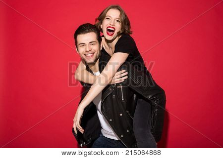 Cheerful young punk couple rejoice together and looking at the camera over red background