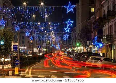 Christmas decoration illuminations and red lights of bypassing cars on evening street of Alba, Italy.