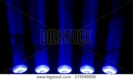 Blue spotlight and smoke on black background. Abstract dark background with bright blue stage spotlights. Lights and smoke. Row of blue lights from a stage