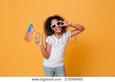 Portrait of a happy little african girl in sunglasses holding american flag and showing victory gesture isolated over orange background