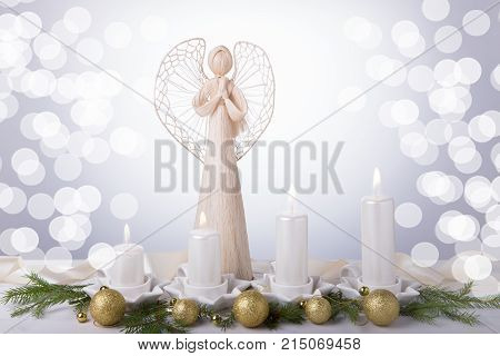 A white angel and four white Advent candles, Christmas tree branches are decorated with golden balls. The imminent background of Advent and Christmas