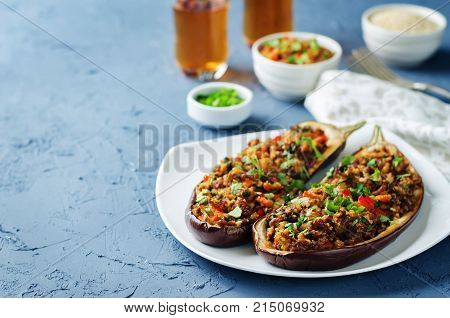 Minced meat quinoa vegetables stuffed eggplants on a stone background