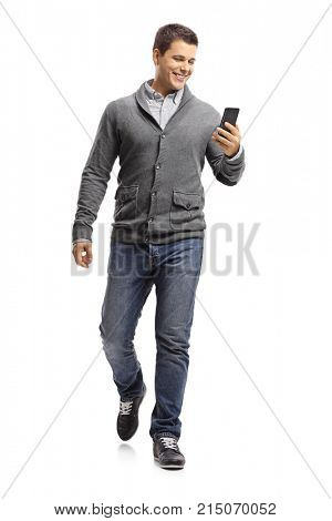 Full length portrait of a young guy using a phone and walking towards the camera isolated on white background