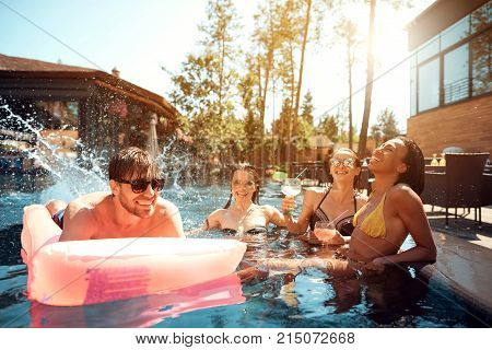 A company of young people is resting by the pool. They are friends, they are very happy, they are smiling at this party. Outside the summer and the sun shines.