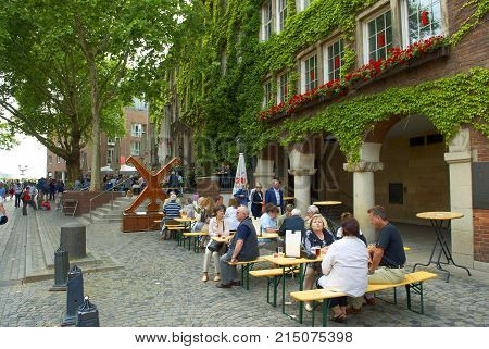 DUSSELDORF, GERMANY, JUN.13, 2010: Classical German open air outdoor beer restaurant tavern cafe with eating people tourists at green house wall. Open outdoor beer restaurant Famous outdoor restaurant