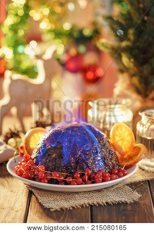 Still life with Christmas pudding flambe on rustic table