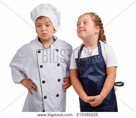 Little cook in a cap and his assistant girl in an apron looks at him on a white isolated background