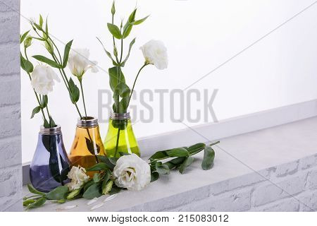 Japanese roses are white in small blue, orange and green vases on the windowsill with disgraced petals and a white rose