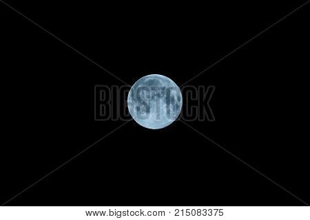 Full moon blue with craters on black sky