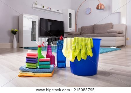 Blue Colored Bucket With House Cleaning Products On Hardwood Floor At Home