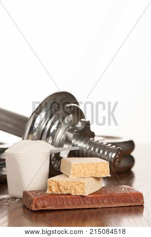 Protein Bar On A Teble With Dumbbell In The Background