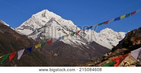 Scene near Namche Bazaar Nepal. Prayer flags and snow capped mountains. poster