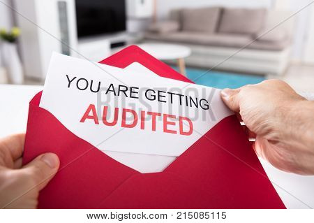 Close-up Of A Person's Hand Holding You Are Getting Audited Card In Red Envelope