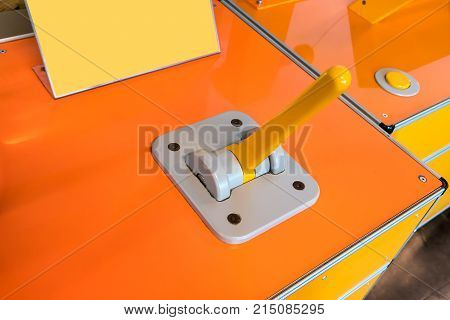 Closed up toggle controller with yellow handle on grey panel of glossy orange box.