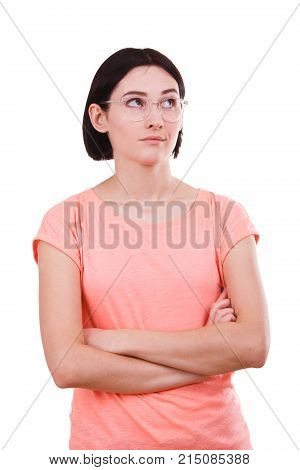 A beautiful girl in a pink t-shirt, with glasses folded hands looking away on a white isolated background