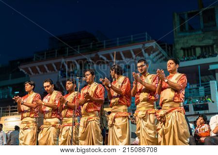 VARANASI INDIA - MARCH 14 2016: Horizontal picture of unidentified Hindu indian men praying at religious Ganga Aarti ritual at Dashashwamedh Ghat in Varanasi India.