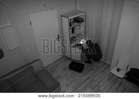 High Angle View Of A Robber Searching In Vacant House For Valuables