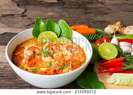 Shrimp soup or Tom Yam goongTraditional food in Thailand contains chili, lime, ginger, galangal, lemongrass, lime leaf, On old wood floor