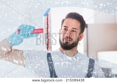 Young Male Janitor Cleaning Soap Sud On Window With Squeegee