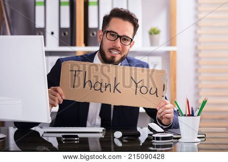 Smiling Young Businessman Holding Cardboard With Thank You Text In Office