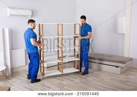 Two Young Men In Blue Uniform Holding Shelf In Living Room